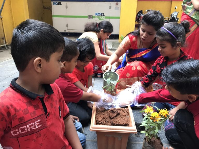 Teacher's helping students in planting trees.